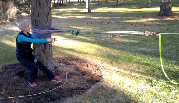 Tensioning a slackline, notice the handled rope grab to make it easier to pull.