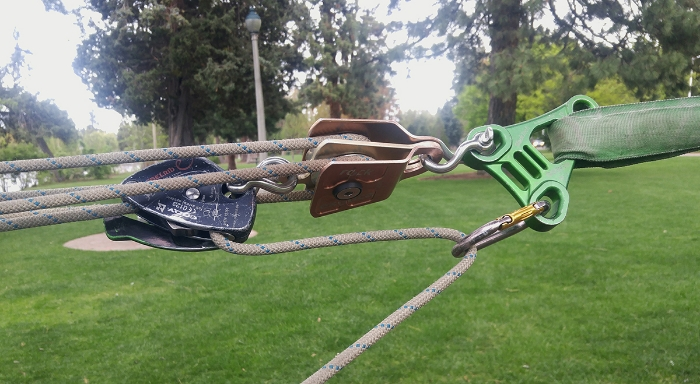 Using a carabiner as a redirect on the tail of the tensioning rope. This give more control when releasing tension.