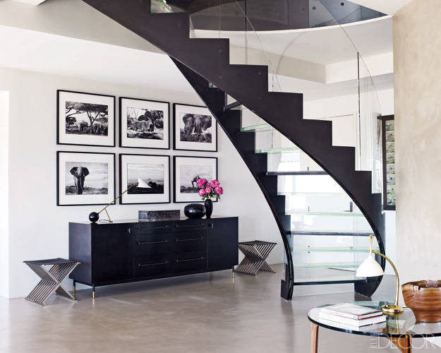 elle-decor-black-and-white-apartment-foyer-entry-hall-glass-stairs-staircase-framed-prints-gallery-wall-gray-cement-floors-cococozy-modern-design.jpg