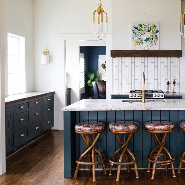 Jewel toned lower cabinetry combined with bright airy whites, gives this light filled kitchen personality while allowing for layering in art and textiles.