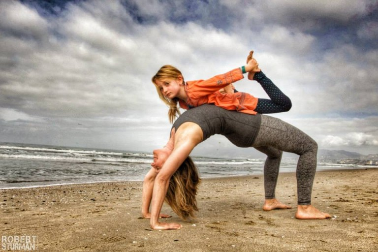 Amy Armstrong   in Upward Bow with her daughter, Sophie, in Bow Pose, on Venice Beach.