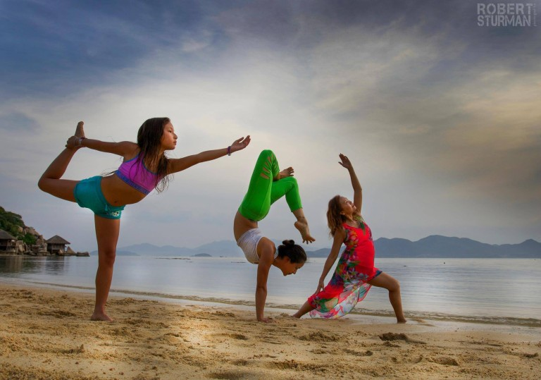 Three generations of yogis. In the middle, Briohny Kate-Smyth in a Handstand, pictured with her daughter, Taylor in Dancer's Pose and her mom, Pam in Peaceful Warrior (Viparita Virabhadrasana), somewhere off the coast of Vietnam.