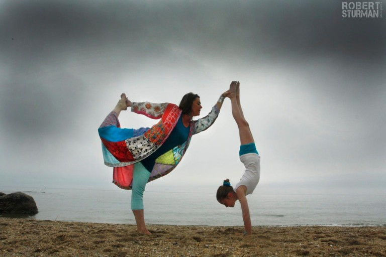 """Seashore home-schooling"" in the North Atlantic.   Mary Vernal   in a Dancer's Pose, supporting her daughter's handstand."