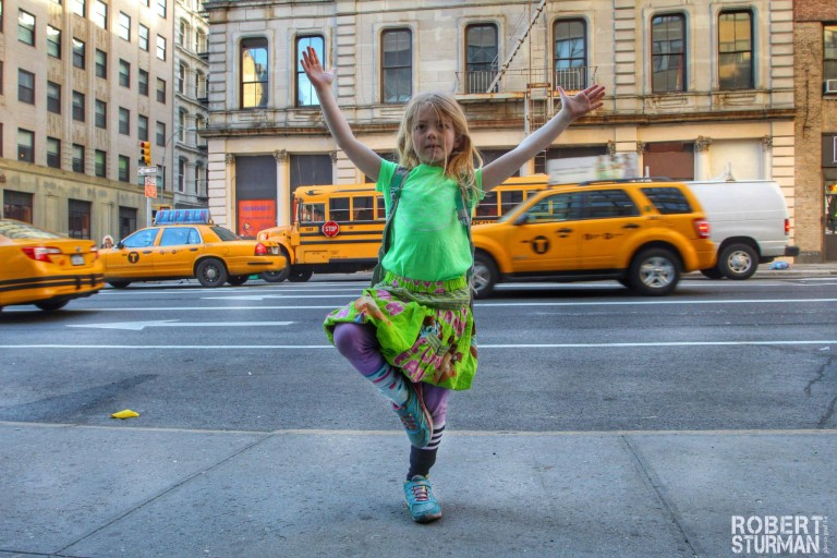 Little Isa on her way to school in Manhattan, in a confident Tree Pose.
