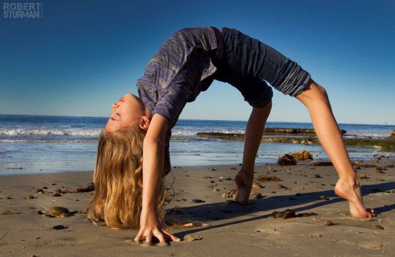 Eleven-year-old, Grace, in Upward Bow (Urdhva Dhanurasana) at Swamis Reef in Encinitas, Calif.   Grace and her yogi-mom Kira founded   KiraGrace clothing  .