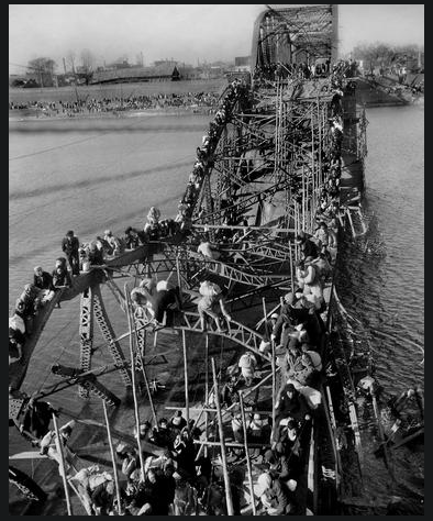 Refugees crossing a wrecked bridge (Source:  AP Photo/Max Desfor)