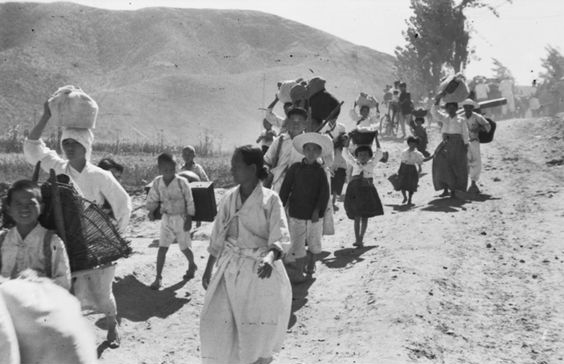 A stream of civilians flee their homes, carrying their possessions on their backs, 1950 (Source:  Australian War Memorial)