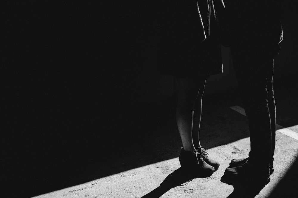 sunlight blasts through an opening to cast hard light on a man and woman's legs.