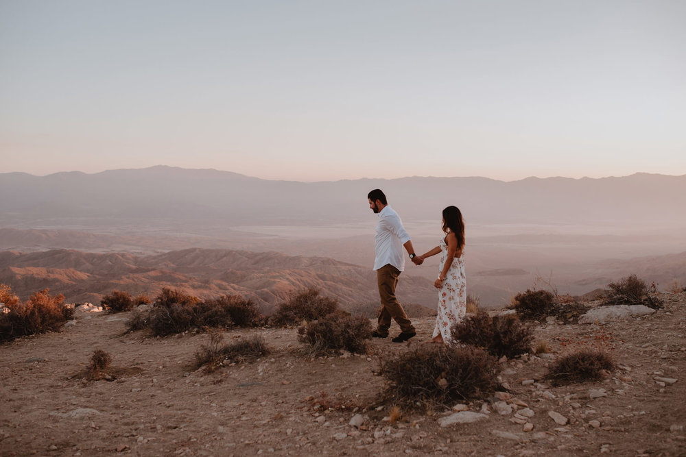 A couple walking holding hands at sunset in Joshua Tree