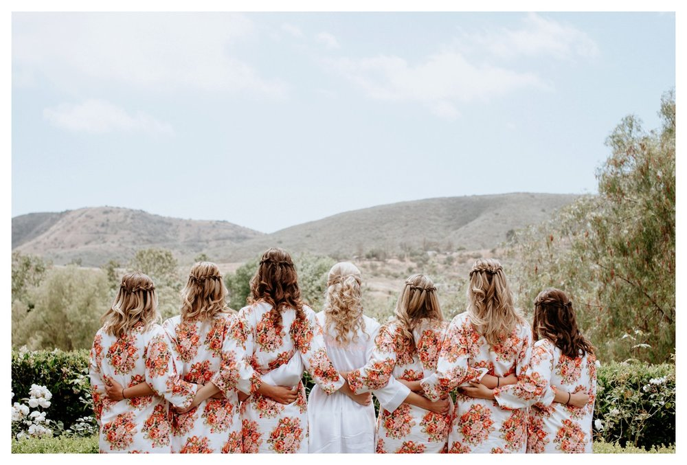 A group of bridesmaids huddle in their trendy silk robes