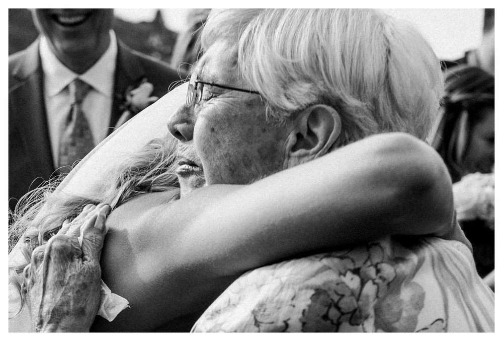 A bride hugs her grandmother during her wedding ceremony.