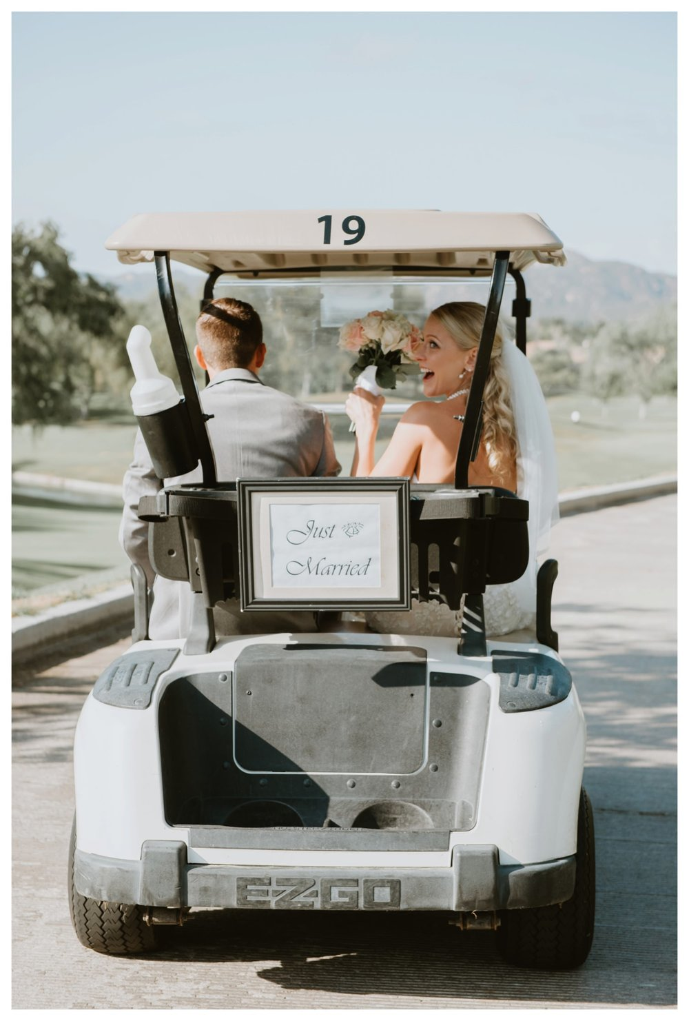 The just married couple make their fun get away in a golf cart.