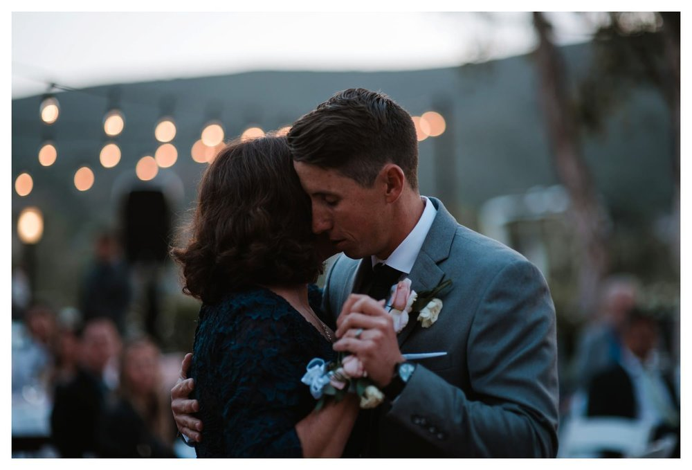 A groom slow dances with his mother as she gently cries tears of joy.