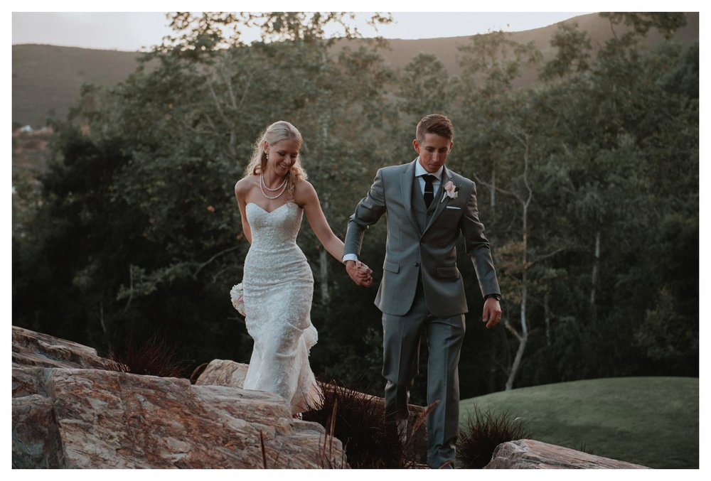 A groom leads his bride across a rocky path during sunset in San Marcos, CA.