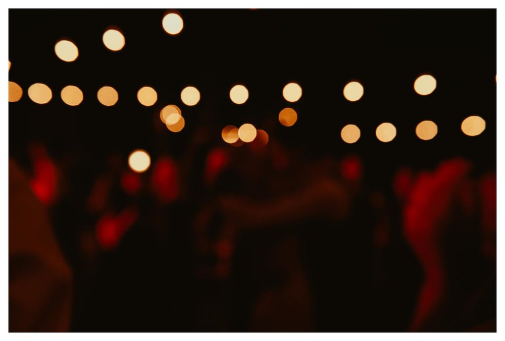 The twinkle of bokeh balls looms over a wedding dance floor.