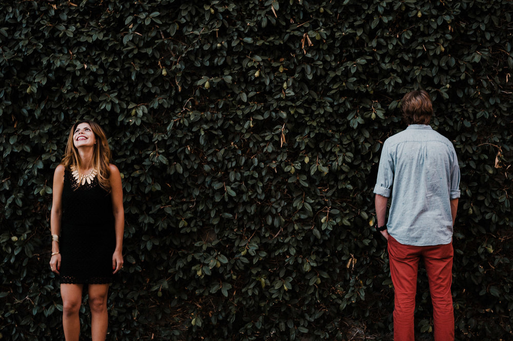 A woman laughs as her fiancé faces towards a wall of bushes instead of facing towards the camera and smiling for a picture.