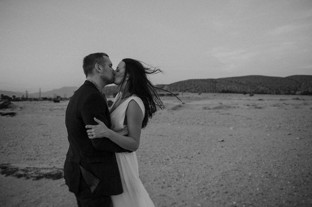 A man an woman celebrate their Palm Springs wedding with a kiss in the desert.