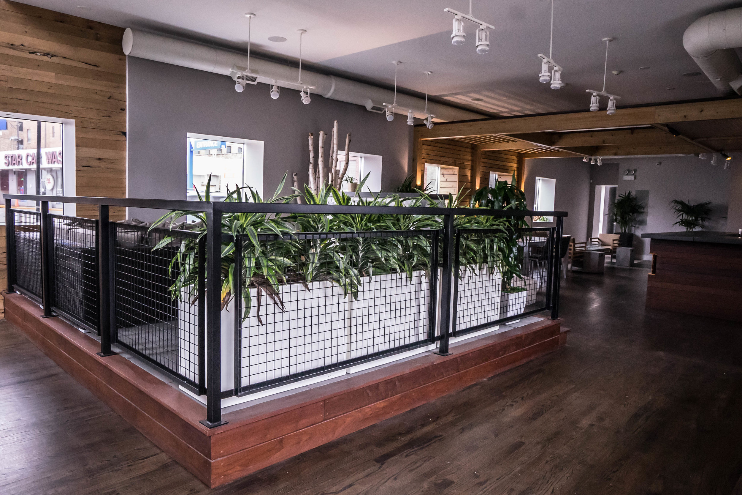As you enter the office, you walk into our showroom which features a slightly raised 'deck' with railings, plantings, tiles, furniture, and a stone fireplace (behind the plantings).