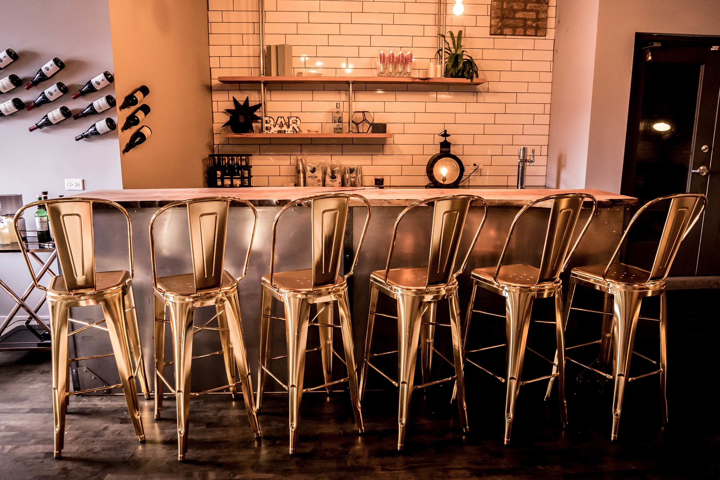 The whole bar has a super industrial feel with metal conduit shelves, a raw wood slab bar top, and metal cladding around the entire base of the bar. The golden metallic chairs demand a second glance as well.