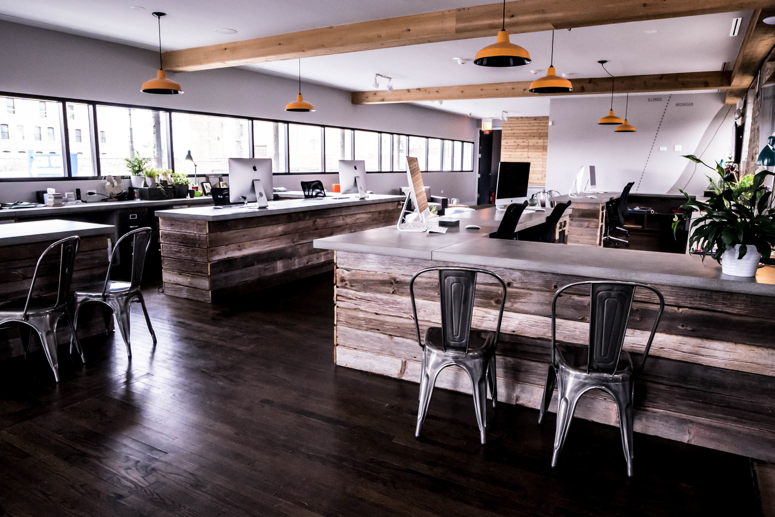 The new work space has desks that are cladded in reclaimed barn wood, all with concrete countertops and orange spotlights hanging above each person's spot.