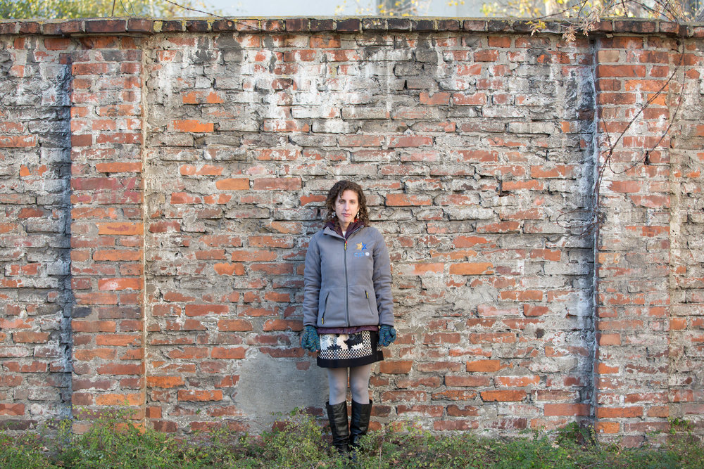Shoshana stands in front of the wall of the Warsaw Ghetto on the 2015 Together, Restoring their Names trip to Poland.