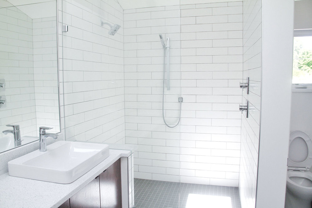 White tile bathroom, with full size shower (tile accent), white quartz countertop and gray tile flooring in Portland, OR