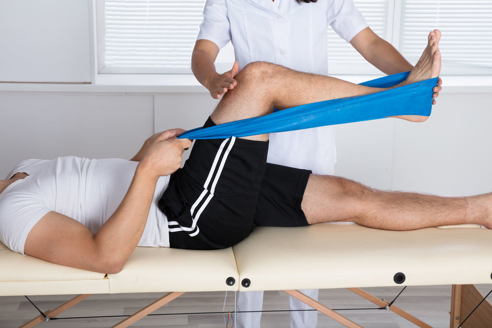 86387112_L_Physical_therapy_workout band_Men_therapist_lay down_feet_leg.jpg