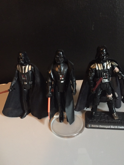 my vintage 1977 Darth vader flanked by newer versions.  there is something still simplistically ELEGANT about that first darth vader figure.
