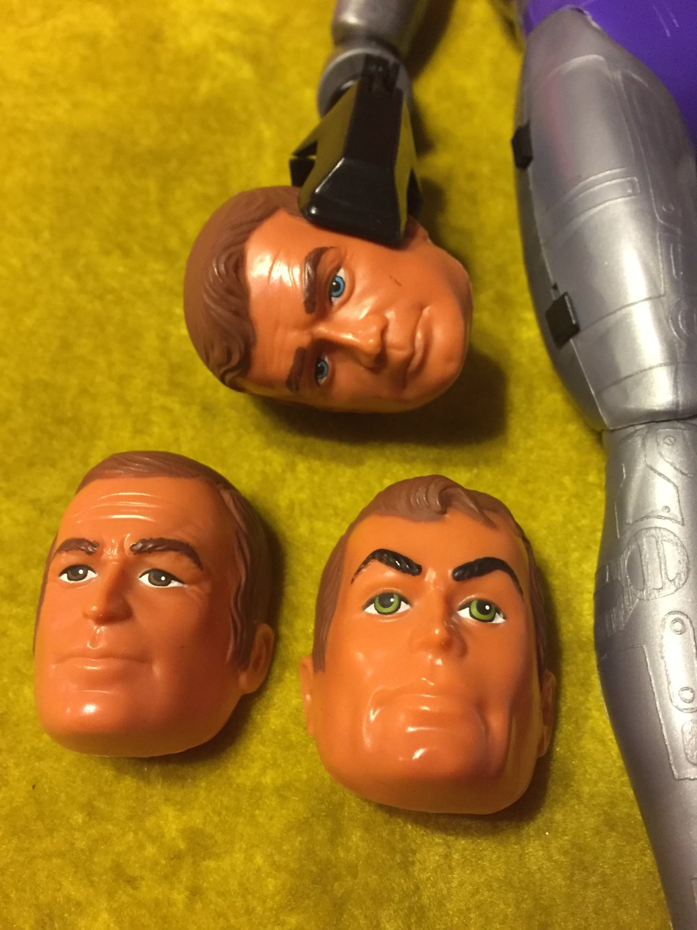 in the claw grip is the bionic man steve austin, then left to right:  Oscar goldman and maskatron human face.