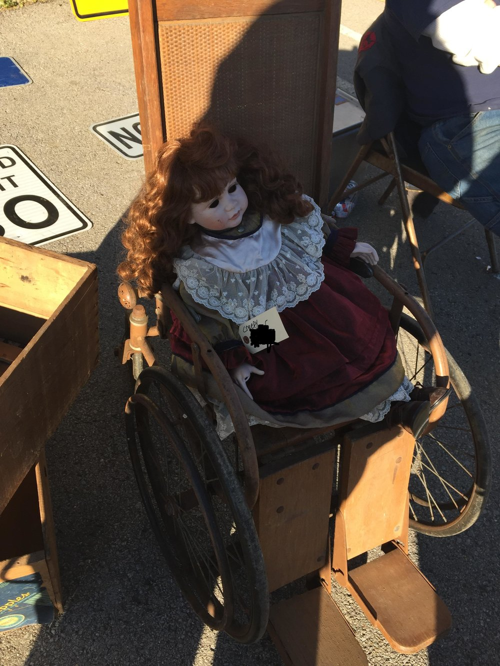 creepy eyeless doll in antique wheelchair.