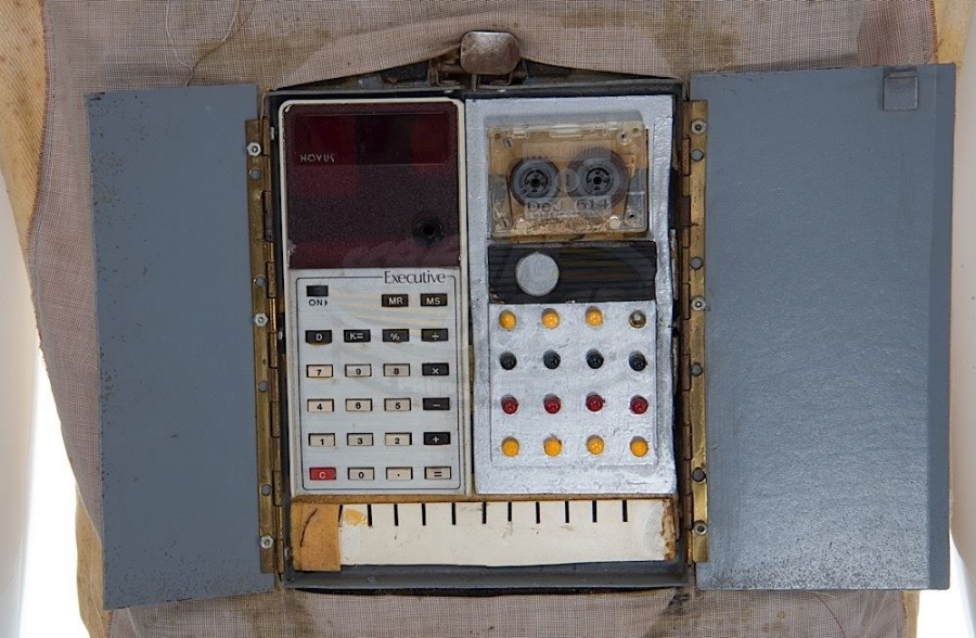 "here is yoyo's actual ""computer panel"" which seems to actually be a calculator, a cassette tape, a radio knob, and some random lights built into a 1970s era fuse box."