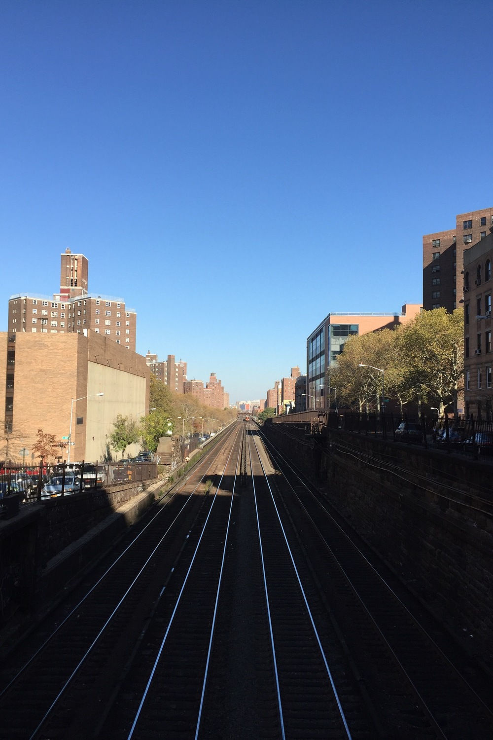 Looking north on 97th Street and Park avenue where the train tracks go underground at midday. A train approaches - November 16, 2015