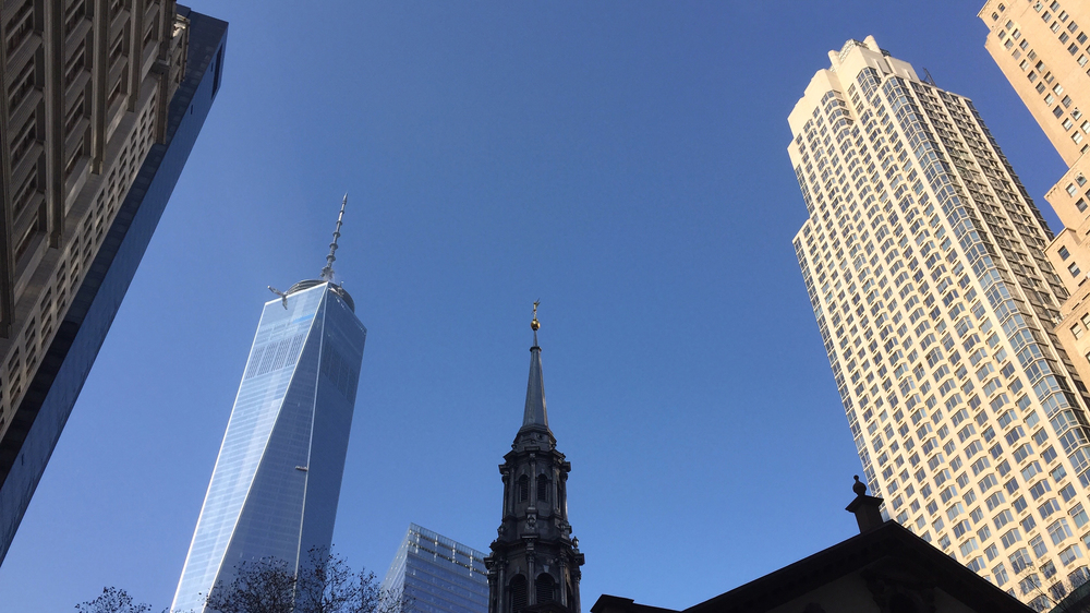 Trinity Church, once the tallest building in Lower Manhattan, is engulfed by modern skyscrapers of various generations on a clear December day - December 10, 2015