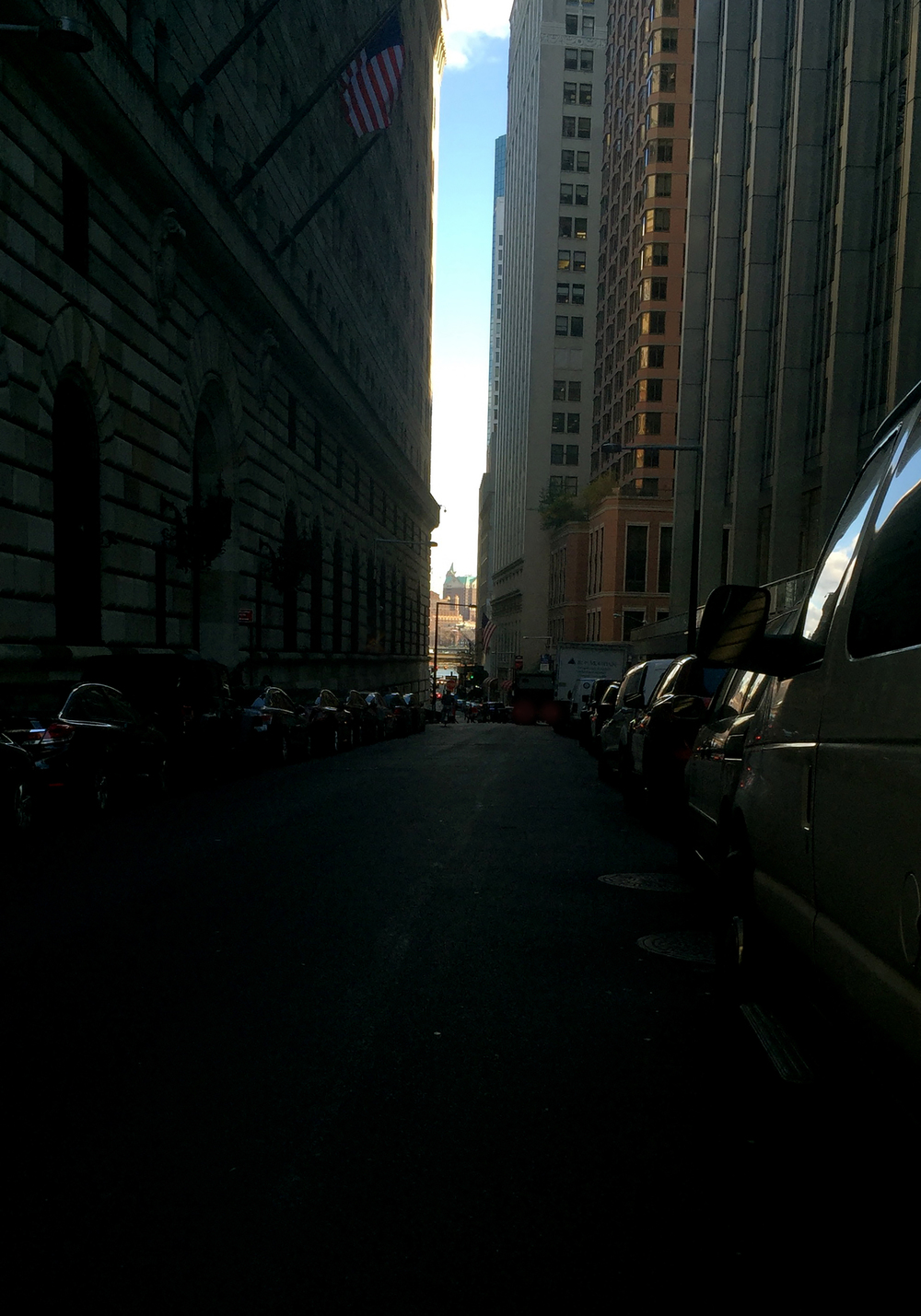 Looking east down Liberty Street on Nassau Street, draped in shade from the skyscrapers, with the sun showing on the water in the distance - November 23, 2015