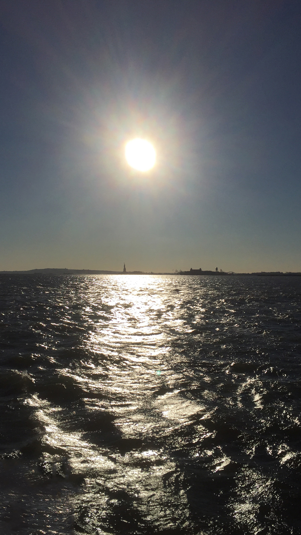 The Statue of Liberty blocks out the afternoon winter sun on the Hudson River, on a cold day - January 4, 2016