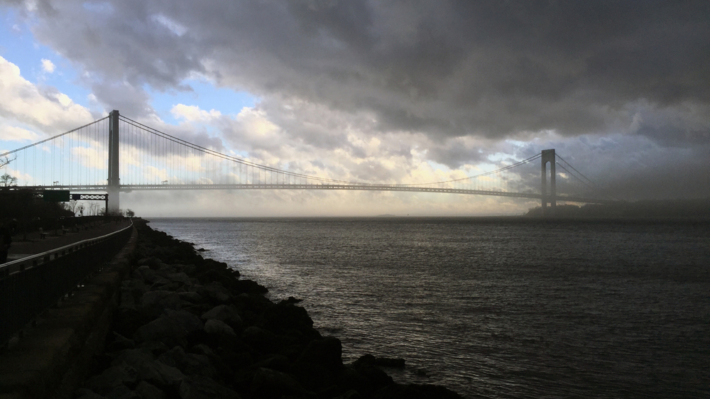 The Verrazano-Narrows Bridge peaks through quick-moving storm clouds on a  warm winter afternoon - January 10, 2016