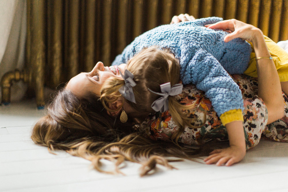 Mother holding her baby on the floor of their Los Angeles home.