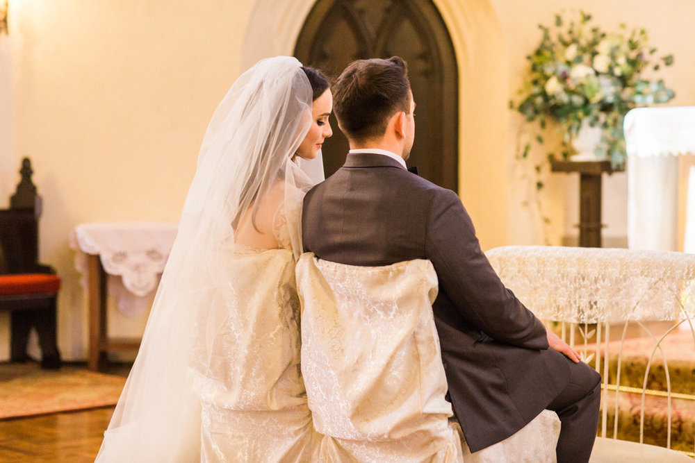Couple sitting at the altar right after saying their vows at St Margaret Mary's Church in Oakland, California.