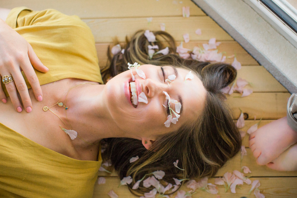 Mother with flower petals on face during family photography session in Albuquerque, New Mexico.