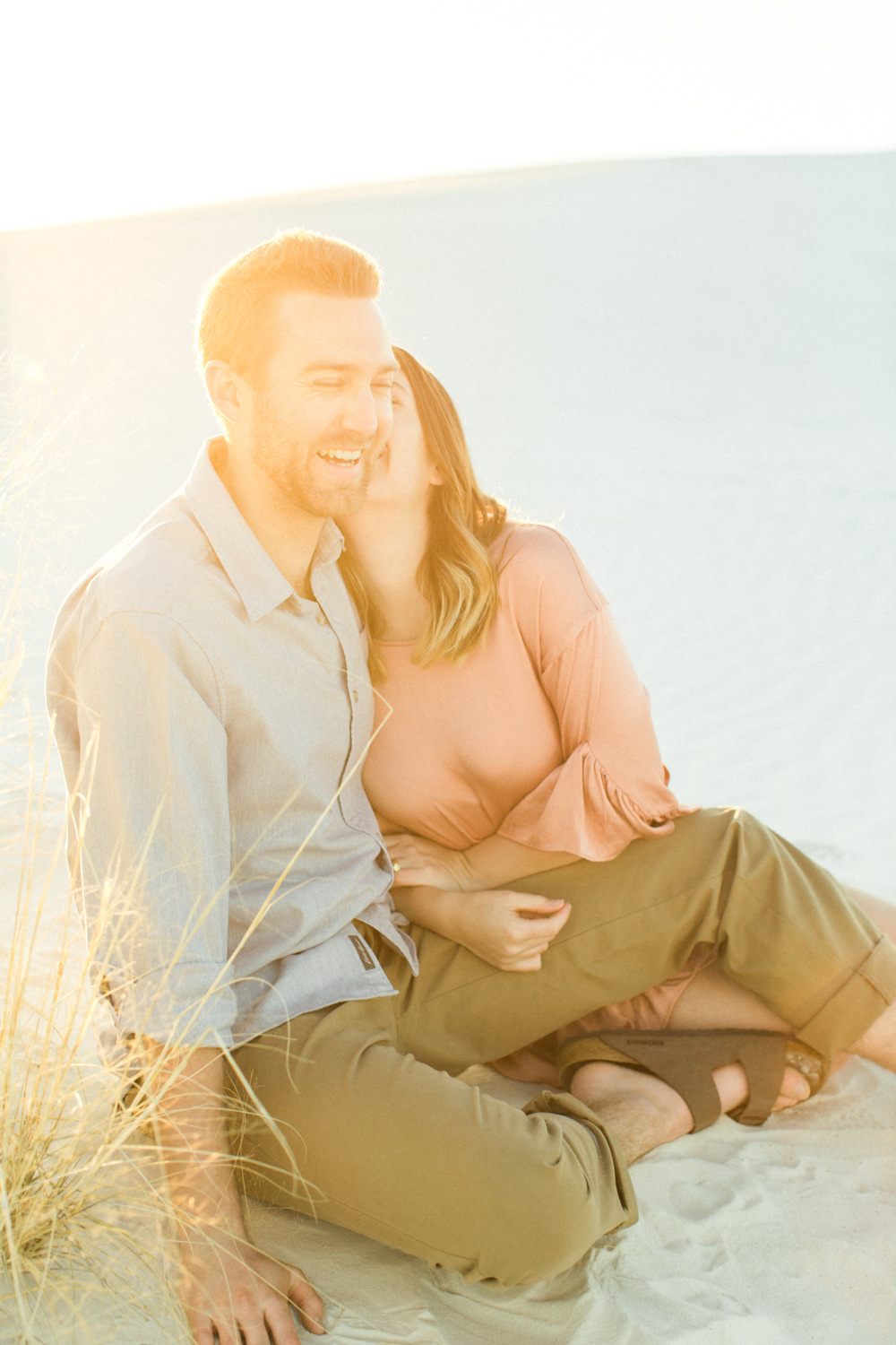 Guy laughing during engagement session in white sands, New Mexico.