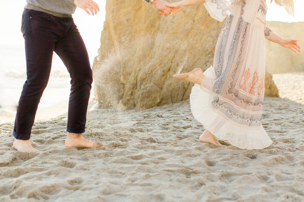 Couple running through sand at El Matador Beach in Malibu captured on film.