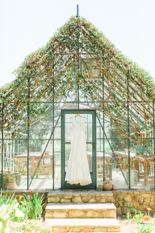 Wedding dress hanging off light filled greenhouse in Ojai, California.