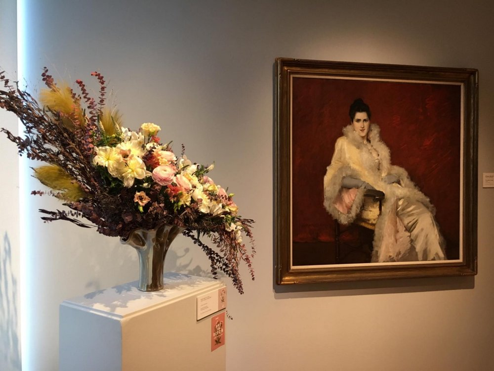 """Art In Bloom Arrangement displayed in the GRAM with it's painting, """"Lady in Opera Cloak.""""  Photo credit Jim Winslow + Featured in Cultured.GR"""