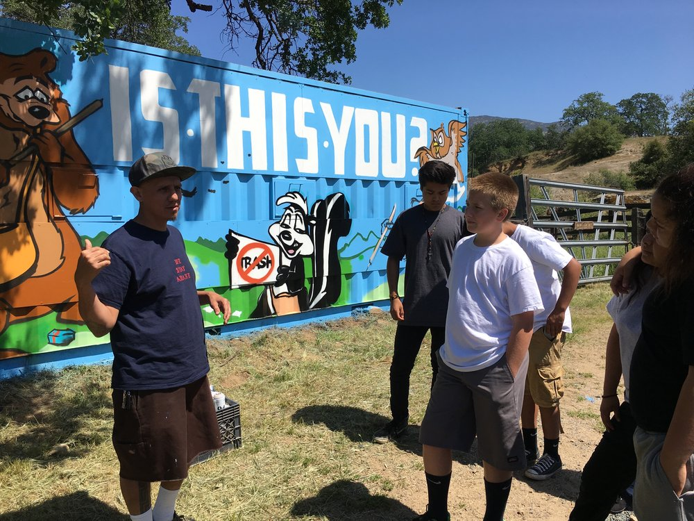 Erik Gonzalez leads aerosol art workshop with students from Vine St. Community Day School. The recycling container is located off of highway 190 as one enters the Sequoia National Forest boundary.