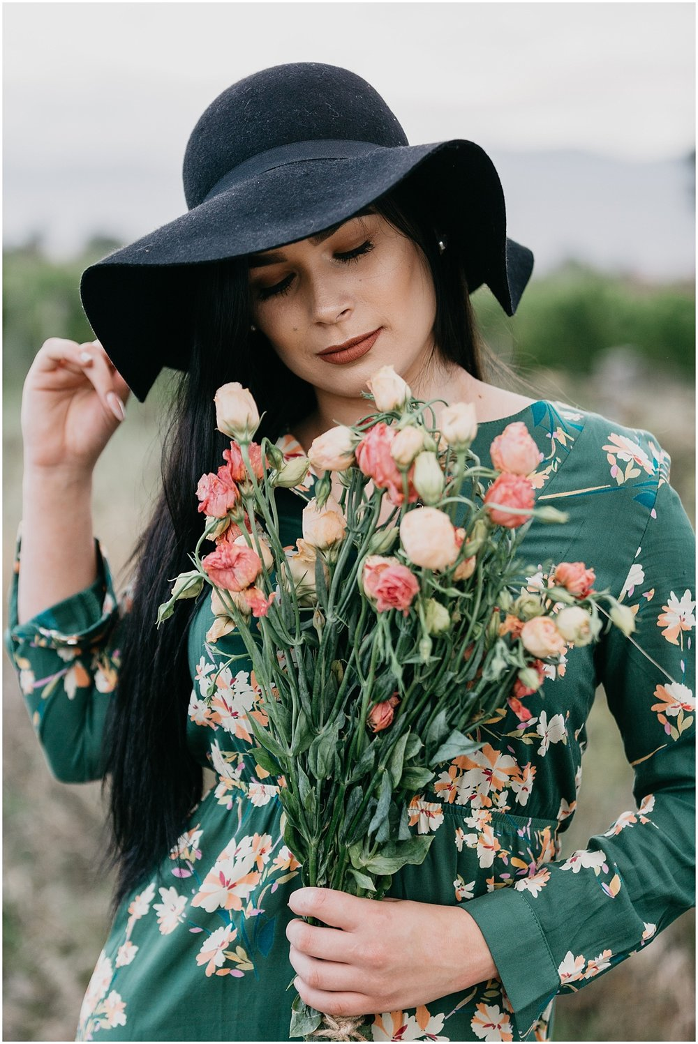 Woman in black hat deep in thought holding bouquet of flowers