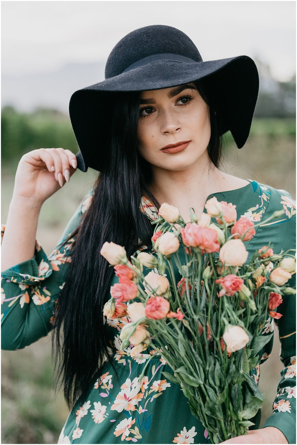 Woman in green dress holding black hat and flowers