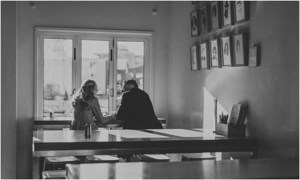 Couple- holding -hands -in- cafe- window
