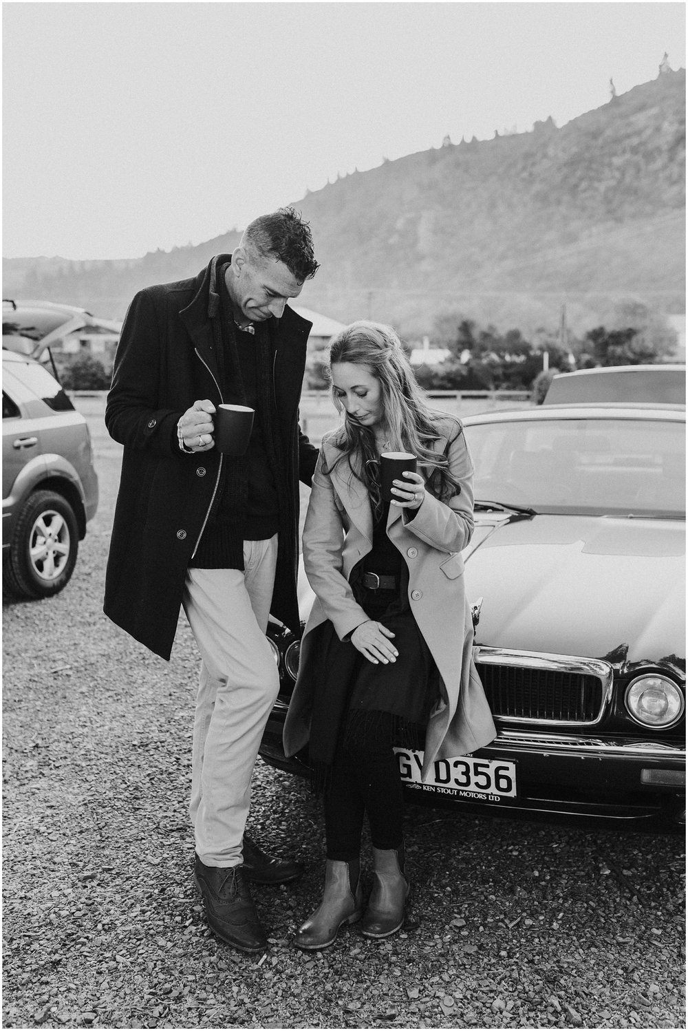 Couple by car drinking coffee