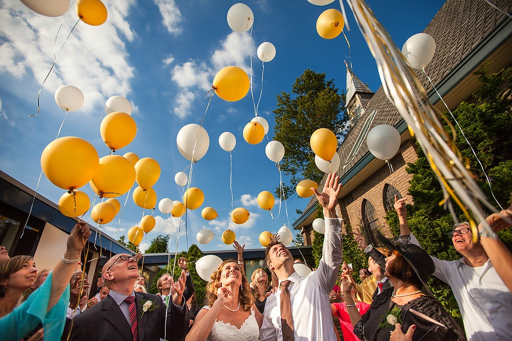 Bruidsfotograaf in Rotterdam tijdens het oplaten van gele ballonnen