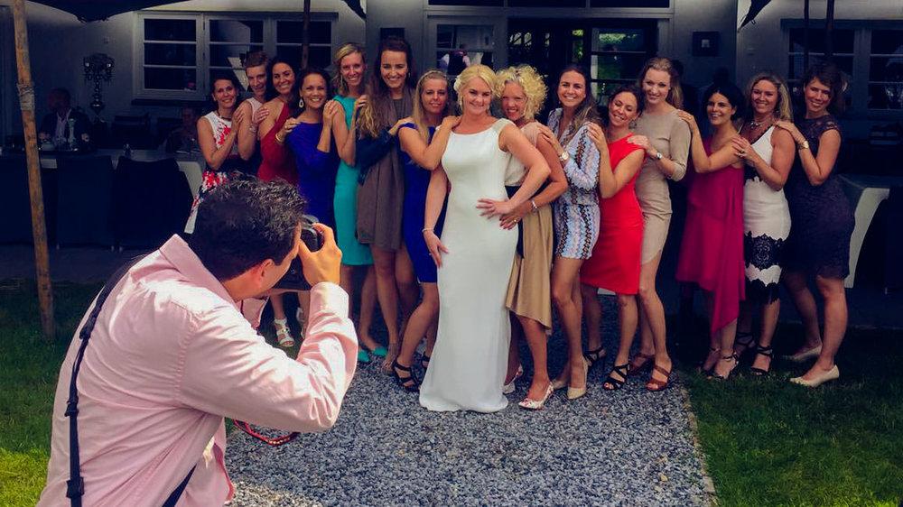 trouwshoot bruidsfotograaf Stefan Segers tijdens groepsfoto geholpen door de ceremoniemeester
